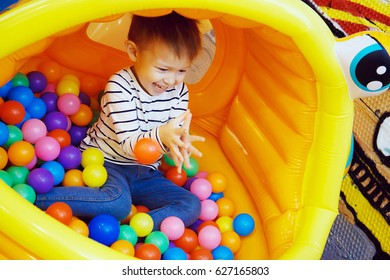 Boy playing with colored balls in the bouncy house at the Playground in the room. Colorful plastic balls, the joy on a child's face, a playful and funny guy.