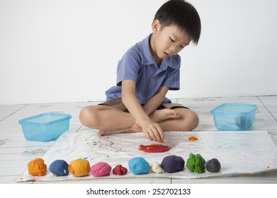 A boy playing colorful dough on white background