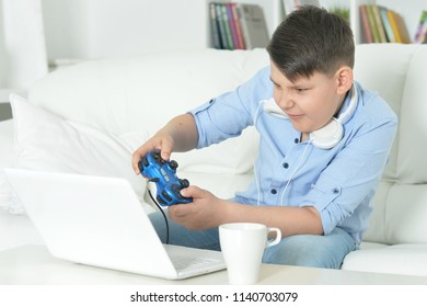 boy playing computer game with laptop