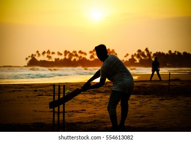 boy playing cricket at sunset on tropical beach in Sri Lanka