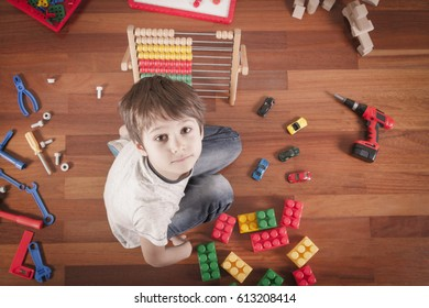 Boy playing with different toys while sitting on wooden floor in his room. Top view