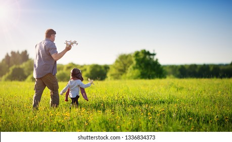 Boy playing with father in aviator hat with old plane at countryside