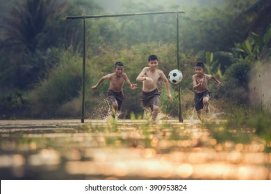 Boy playing football with kicking soccer ball