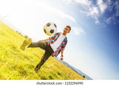Boy playing football in a meadow, having fun