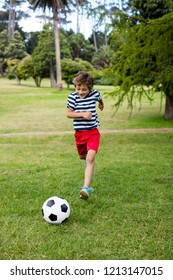 Boy playing football in park on sunny a day