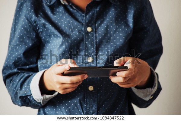 Boy playing games on smartphones, Boy hand holding a smartphone