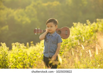 Boy playing guitar at the Natural sunsets.