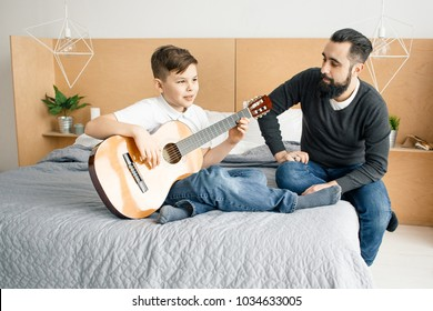 Boy playing guitar while seating on bed with father