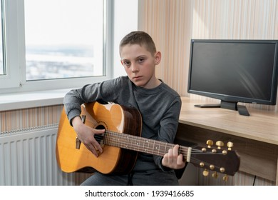 boy playing guitar while sitting by the window in music class