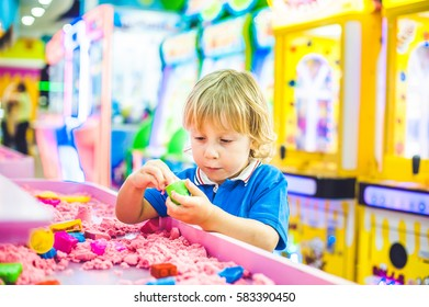 Boy playing with kinetic sand in preschool. The development of fine motor concept. Creativity Game concept.