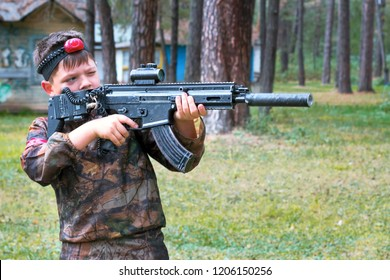 Boy playing laser tag outdoors. Military tactical game