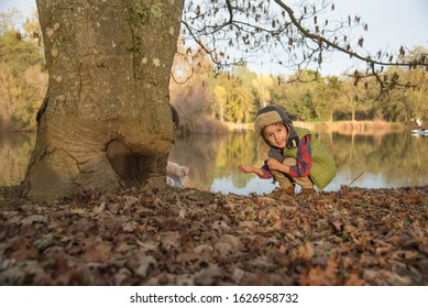 Boy playing with leaves near lake