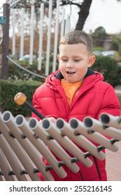 Boy playing a metal xylophone in downtown Sedona, Arizona