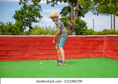 boy playing mini golf. child with a putter on golf course
