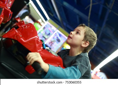 Boy playing in motorcycle simulator at indoor playground
