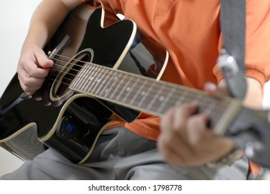 Boy playing music with black guitar