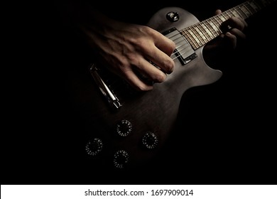 boy playing music on guitar, closeup