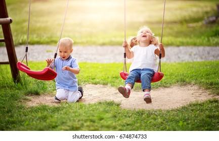 Boy and boy playing on the backyard on swings
