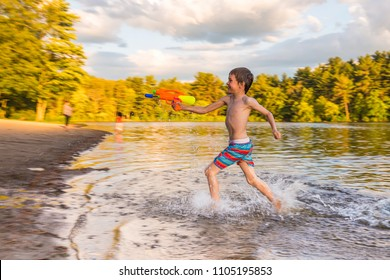 boy playing on the beach with a water gun. child during a water fight with water pistols. water fun