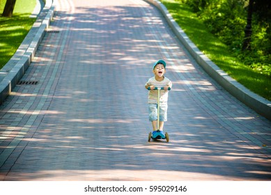 Boy playing on his scooter in the local park. happy smiling kid