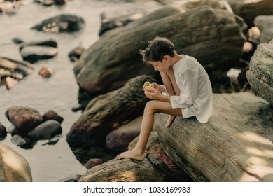 the boy is playing on rocks on the ocean shore