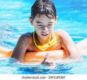 Boy playing on the swimming pool pressing the water with hands and splashing water around.