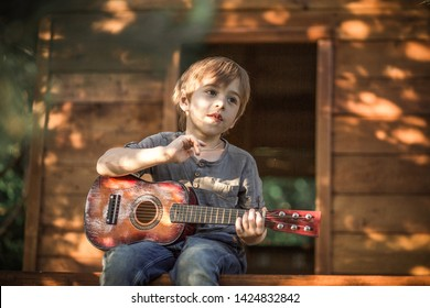 A boy is playing on the ukulele in the tree house. Image with selective focus and toning