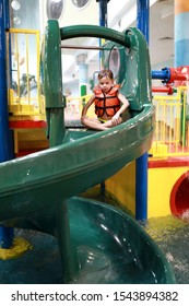 Boy playing on water slide in aquapark
