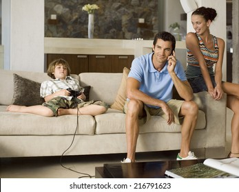 Boy playing playstation, father on the phone.