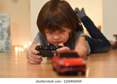 Boy playing with a red car on remote control. Child play with a toy car