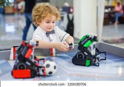 boy playing in robots football, smiling curly caucasian face, two robots on the table, remote control, robot and kid, education, science and people concept, children, technology