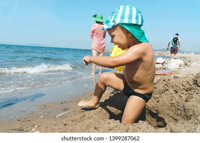 boy playing in sand at sea coast