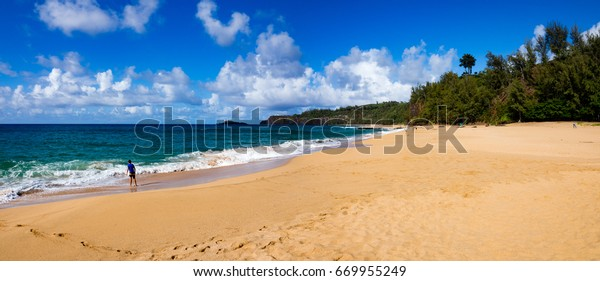 Boy playing at Secret Beach (Kauapea), Kauai, Hawaii, USA, summer day, sunny, Kilauea ilighthouse n distance