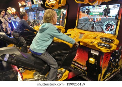 Boy is playing slot machines. Moscow 2012. Kid playing arcade simulator machine at an amusement park. Boy on amusement bike at indoor playground.
