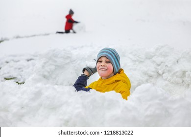 boy playing in a snow fort. snowball game. The concept of winter fun