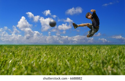 Boy playing soccer against the sky