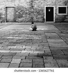 Boy playing with soccer ball in Venice Italy black and white