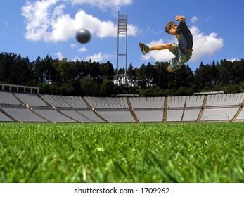 Boy playing soccer in a green grass field
