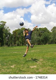 Boy playing soccer in a green grass field with blue sky above
