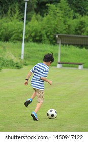 a boy playing soccer in the park