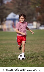 Boy playing soccer in the park - Authentic action with soccer ball - copy space top - portrait format