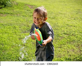 boy playing with a squirt gun squirting photographer