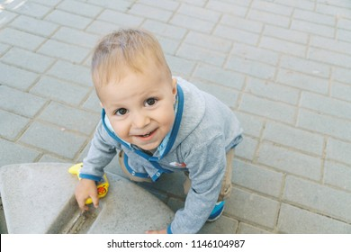 boy playing in street with yellow toy