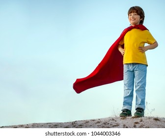 Boy playing superheroes on the sky background, child superhero in a red cloak on a hill