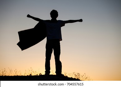 Boy playing superheroes on the sky background, silhouette of teen superhero in a raincoat on the hill