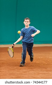 Boy playing tennis on a dross court, some motion blur on the arm as he hits the ball