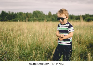 boy playing with a toy airplane in a field