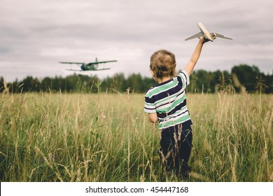 boy playing with a toy airplane on a background of an airplane landing