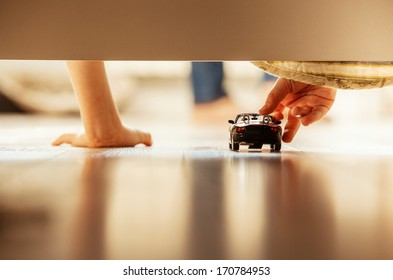 Boy playing with toy car overhang from the bed