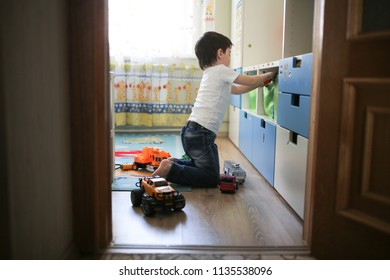 boy playing with toy cars in a child's room, the concept of childhood and safety